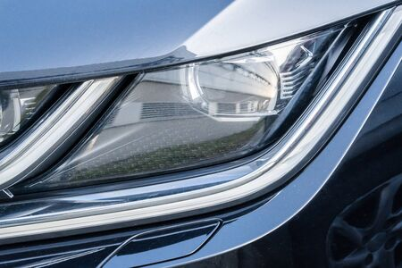 Led headlight of a gray modern car. Modern trends in the automotive industry. Head optics of the machine