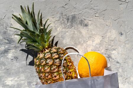Pineapple and orange in a white paper bag on a gray non-uniform background. Vitamin-rich tropical fruits. Healthy diet