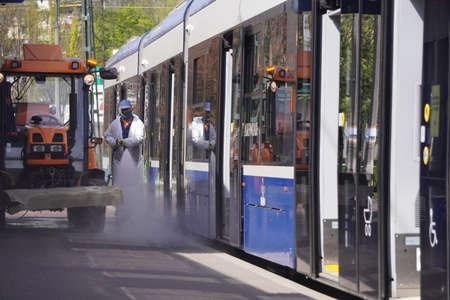 Cracovie, Pologne 23.04.2020 : Assainissement des bus et des tramways contre la contamination, les bactéries et les virus pendant la pandémie de coronavirus. Des hommes en tenue de protection lavent les transports publics et les rues avec un antiseptique