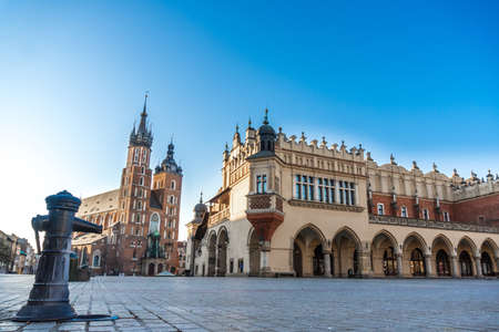 Krakow, Poland 20.04.2020: empty, deserted main market square in center of city at dawn against blue cloudless spring sky. no tourists, closed restaurants and shops. Closed state borders
