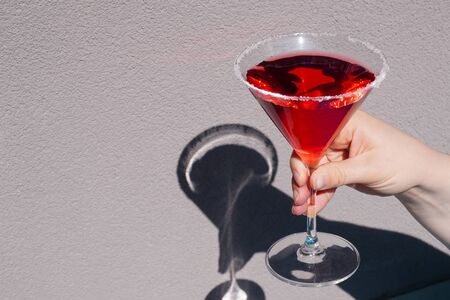Red cocktail in a Martini glass on a gray background. Red liquid in a glass. Glass beaker.