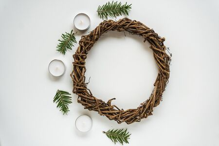 Base for Christmas wreath or nest for Easter on white background, candles and branches of spruce. Handwork with creativity, needlework with children. DIY, decoration to holidays. Flatly with copyspace Banque d'images