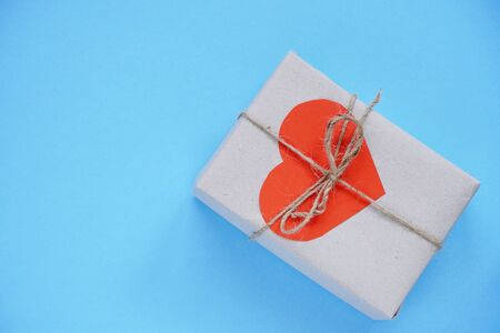Gift box wrapped in craft paper with jute rope and bright red heart on a light blue background. Holiday concept for Valentine s day. Presents with love. Flat lay with copyspace.