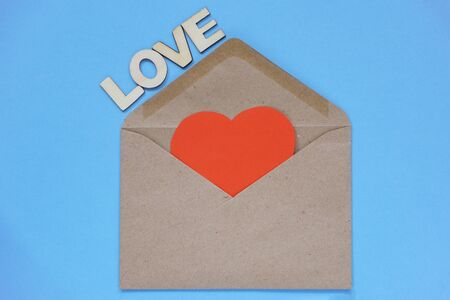 A red paper heart lies in a craft envelope on blue background. The concept of love and letters, recognition. Blank for designers, copy space. Love is written in wooden letters
