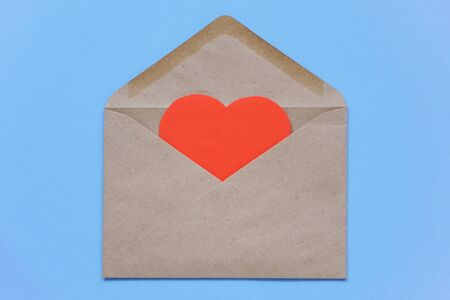 A red paper heart lies in craft envelope on a blue background. The concept of love and letters, recognition. Blank for designers, copy space.