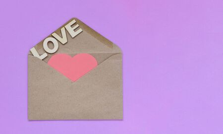 Pink paper heart lies in a craft envelope on light purple background. concept of love and letters, recognition. Blank for designers, copy space. Love is written in wooden letters