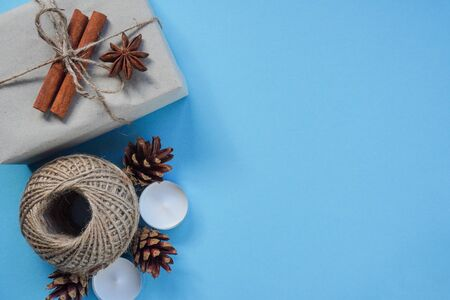 Christmas layout on blue background, top view. Flatley, Packed in craft paper, tied with string with cinnamon sticks and anise.Candles and cones create comfort in cold, decor.