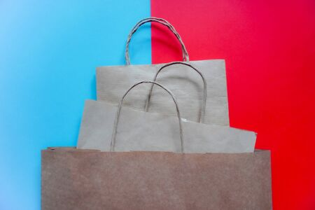 Top view of empty craft paper bags on blue and red background. Flat lay on contrast background, zero waste. Garbage recycling. Template or Mockup for designers.stop plastic. pyramid of packages Фото со стока