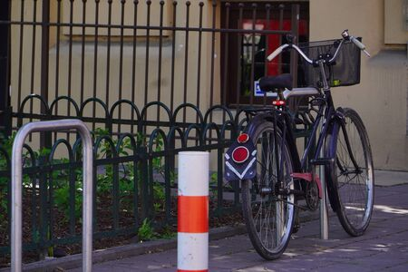 One old bike is fixed to a metal structure for Parking bicycles or scooters, environmental transport in city. Moving by bike every day. bicycle at street parking outdoors