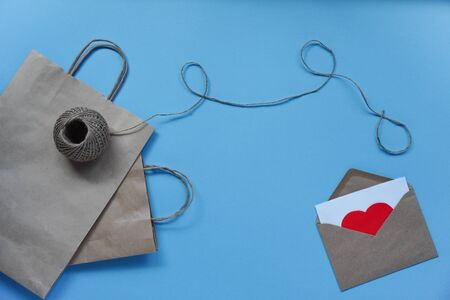 raft paper bag with string and envelope with white sheet and red hearts on blue background. Concept of love, greetings, letters of recognition on Valentine's day and birthday.Flat lay, copy space. Foto de archivo