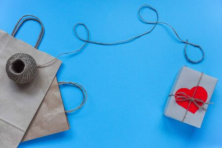 raft paper bag with string and envelope with red heart on box on blue background.Concept of love, greetings, letters of recognition on Valentine's day and birthday. Flat lay, copy space. Фото со стока