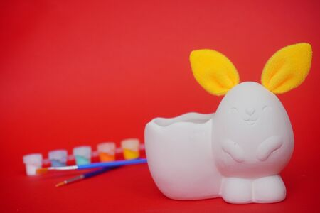 statuette of white figure of bunny or rabbit with yellow ears for decorating, Easter DIY with children. Multi-colored paints and brushes on red background.Minimal easter concept 免版税图像