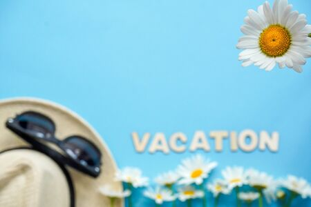 Blurred: straw hat with sunglasses and white flowers daisies on blue background, one Daisy is in focus. Summer flatlay background with traveler accessories.Top view with copy-space. Vacation concept