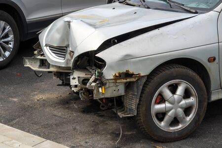 The front part of a grey passenger car damaged in an accident or traffic accident. Broken-down car, insurance payments. Disposal of damaged cars. Repair of machines.