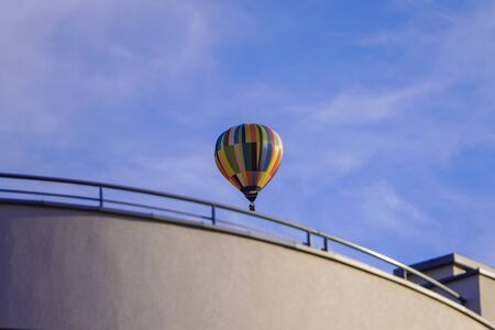 Large bright colored hot air balloon is flying over a house in the city Poland, Krakow. Festival of balloons.