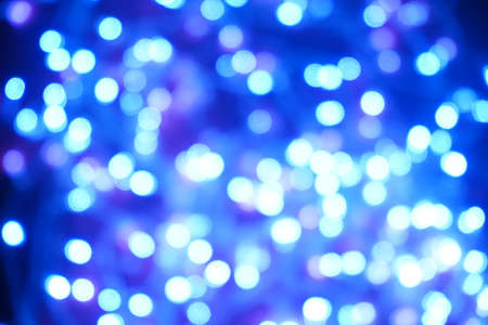 Blue lights on a purple background are blurred. Concept of blank frame,copy space. Christmas or new year flatlay background.