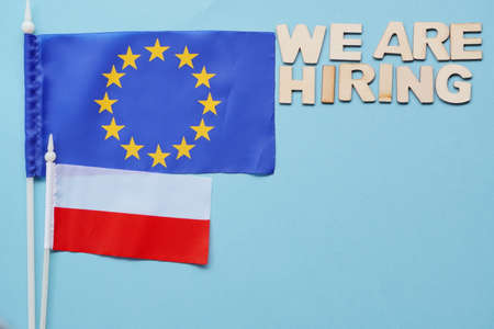 Search for employees, recruitment after crisis and coronavirus. we are hiring-wooden letters on blue background. flatly with copy space. new hiring positions.EU and Polish flags,work abroad Banque d'images