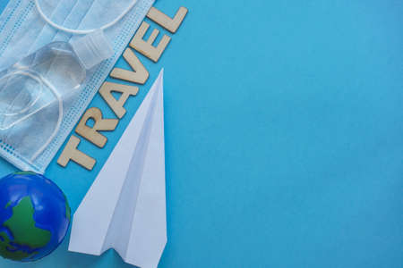 Top view planet earth,mask, sanitizer, paper airplane on blue. Relax on coronavirus. Summer flatly, composition with copy space, safe travel and leisure concept. Wooden word Travel