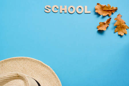 Summer hat and dry oak leaves with Woody school inscription.back to school or kindergarten. summertime, creativity and learn background with Banque d'images