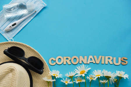 Summer layout with straw hat, daisies and sunglasses, mask, thermometer and sanitizer on blue. Top view of summer traveling and recreation during pandemic coronavirus. relax flatlay, travel at home