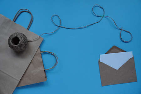 craft paper bag with string and envelope with white sheet on blue background. Concept of love, greetings, letters of recognition on Valentine's day and birthday.Flat lay, copy space.