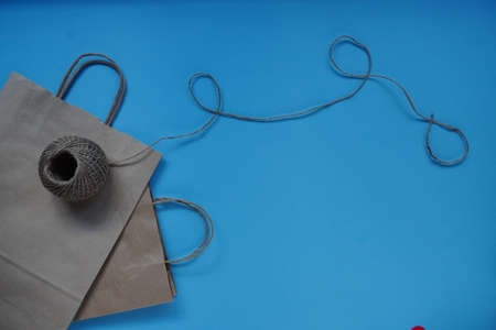 Craft packaging bag with hearts and twine. Flatley on blue background with Copy space. Gifts for holidays, Valentine's day and birthday with love. concept of love, greeting, flat lay.