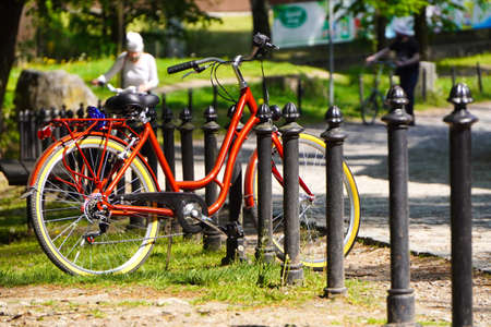 Bright red Bicycle stands at the fence in a green Park on a Sunny day. Moving by bike every day. bicycle at street parking outdoors. use of eco-friendly and sports transport in the city to move Banque d'images