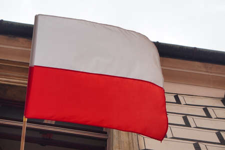 Polish white-red flag in wind on wall of the block or house. Natural Light Selective Focus. building view. 1 of May,November 11,flag or independence or labor day. Government holiday, President voting