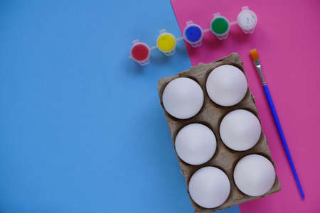 Tray or box of six eggs on blue and pink background, multi-colored paints and brushes. Set for easter DIY children's creativity. Minimal easter concept. Symbol Happy Easter Flat lay