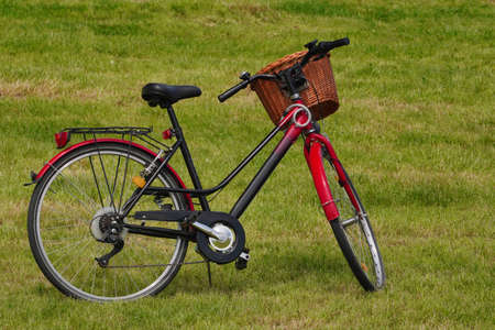red-and-black city Bicycle with a basket stands in a meadow, on the newly mown grass in the Park. Walking and driving in the fresh air in Sunny weather, an eco-friendly form of transport
