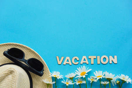 Summer layout with straw hat, daisies and sunglasses and inscription Vacation. Concept of travel and recreation.Flights to sea, rest during coronavirus. Flatly on blue