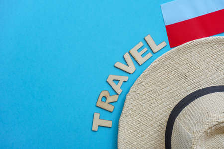 Top view hat,mask, glasses,polish flag on blue. Relax on coronavirus. Summer flatly, composition with copy space, travel and leisure concept. Wooden word Travel