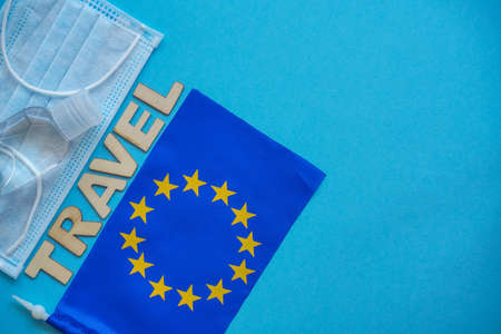 Top view mask, sanitizer, european union flag on blue. Relax on coronavirus. Summer 2020 flatly, composition with copy space, travel and leisure concept.Wooden word Travel Banque d'images