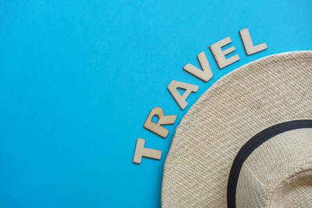 Top view hat and letters on blue. Relax on coronavirus.Summer flatly, composition with copy space, travel and leisure concept. Wooden word Travel Banque d'images