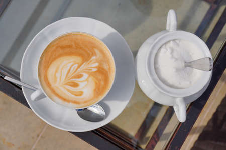 Cup of coffee with milk and flower as decoration, sugar with small spoon in white tableware on glass with metal frame table. Summer relax time,take sunbath