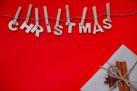 Christmas composition or ornament on red background from wooden inscription Christmas, cones, wooden Christmas tree, candles and branches of spruce. Copy space, space for text, flatly.