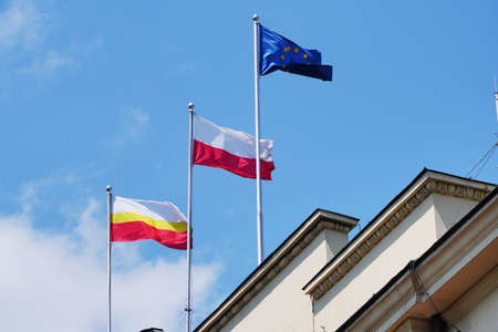 White-yellow-red, red-white and blue flags against the blue sky on the roof of the building. Polish, European Union, malopolska district flags fly on a Sunny day. Banque d'images