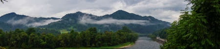 Panorama of the river and mountain view at dawn, fog over the water on a cloudy day. Landscape in Szczawnica, Poland. Beskidy mountains, three crowns trzy korony mountain, Dunajec river Banque d'images