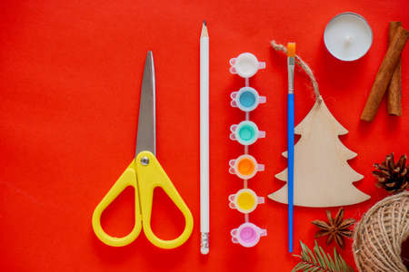 New year DIY background, creativity with children, make a gift with your own hands. Scissors, twine, pine cone, paint brush, wooden spruce on a red background. Home decoration for the holiday
