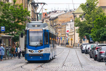 Poland, Krakow 02.18.2020: Old city blue tram on the city street. Eco-friendly urban public transport. urban forestry, protection of the environment.