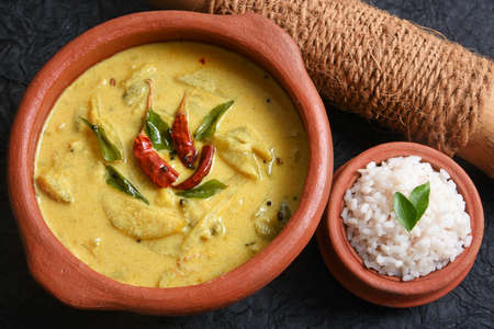 Yellow mango curry or Mampazha Pulissery sweet and sour dish for Onam Sadhya or Sadya Kerala India. organic raw ripe mango, coconut milk, seasoned with curry leaves, mustard, Indian red Kashmir chilli