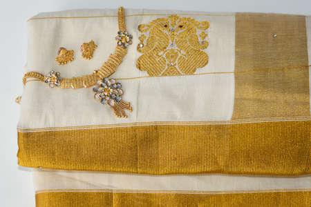 Indian silk sari, handmade white Kerala Sari and gold ornaments, jewellery. woman use this traditional wear on Onam festival, Vishu, wedding in India. multi-colored saree clothing.
