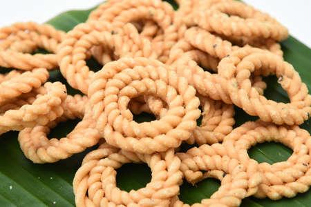 Kerala snack rice Murukku savory, Chakli, Chakali fried snack on banana leaf popular in South India Tamil Nadu, Top view Indian tea time food fried in coconut oil.
