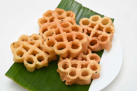 Kerala snack Achappam or rosette cookies fried snack on banana leaf popular in South India Tamil Nadu, Top view Indian tea time food fried in coconut oil.