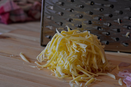 Grated cheese, chopped ham, balls of mozzarella and grater on wooden background