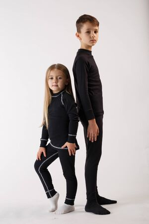 Boy and little girl in thermal underwear on a white background. Sportswear. Archivio Fotografico