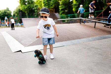 Boy with a skate in a skate park. A boy with glasses learns to skate in stylish clothes. A little extreme