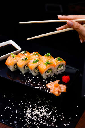 Sushi with salmon. Soy sauce, ginger, red caviar. Roles with red fish.