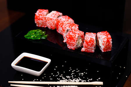 Sushi with salmon. Soy sauce, red caviar. Sushi on a black background. Zdjęcie Seryjne