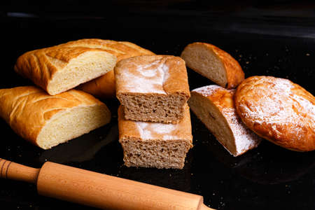 Baking on a black background with a rolling pin. Lots of pastries and bread.